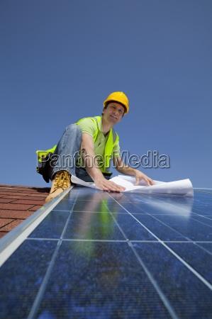 ingenieur holding blueprint auf solarpanel auf