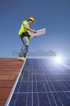 ingenieur untersuchen bauplan auf dem dach