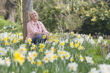 smiling woman sitting against tree trunk