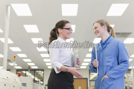 smiling engineer and businesswoman talking in