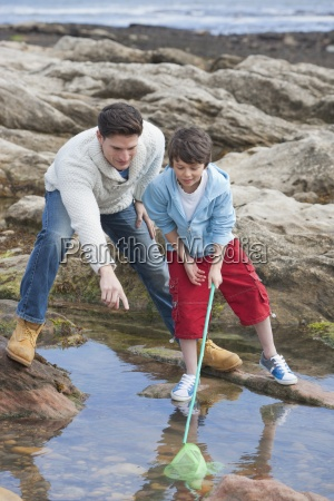 father and son exploring rockpools together