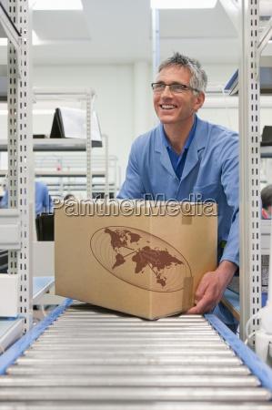 laechelnde arbeits platzierung karton auf foerderband