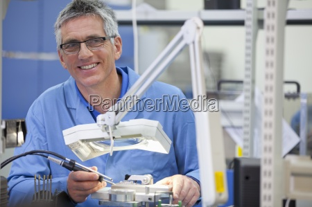 portrait of smiling technician working on