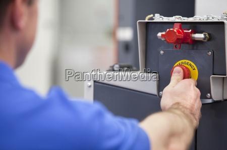 technician druecken notausschalter auf drehmaschine schneidemaschine
