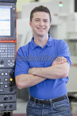 portrait of smiling technician leaning against