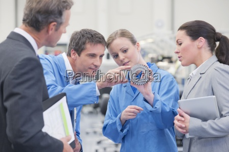 business people and engineers discussing machine