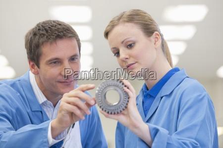 close up of engineers examining machine