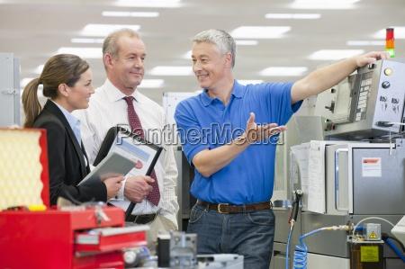 engineer explaining machine to business people