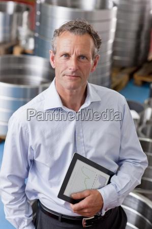 portrait of confident businessman holding digital