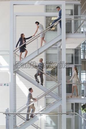 businessman blocking businesswomen on stairs in