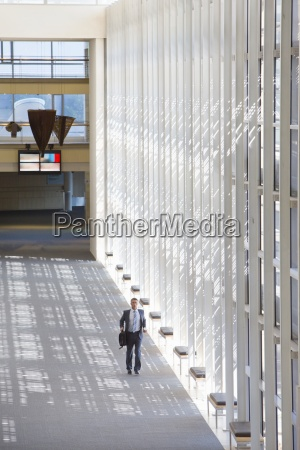 businessman running in lobby of modern