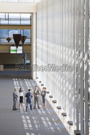 business people talking in lobby of