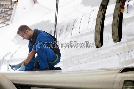 engineer repairing wing of passenger jet