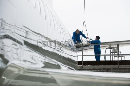 engineers assembling tail of passenger jet