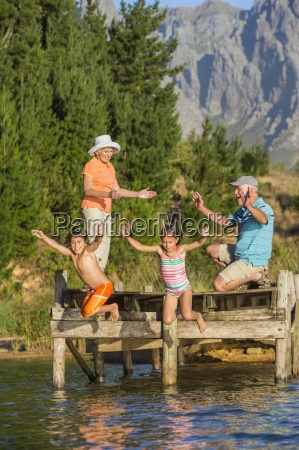 grandparents watching grandchildren jump from dock
