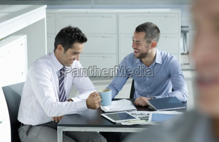 businessmen laughing at table with paperwork