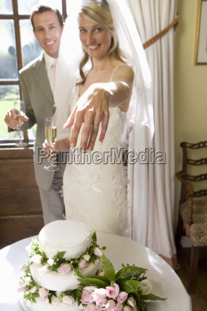 bride and groom by wedding cake