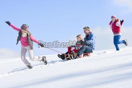 happy family sledding down snowy hill