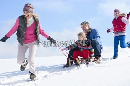 froehliche familie die schneebedeckten huegel hinuntergeschlafen