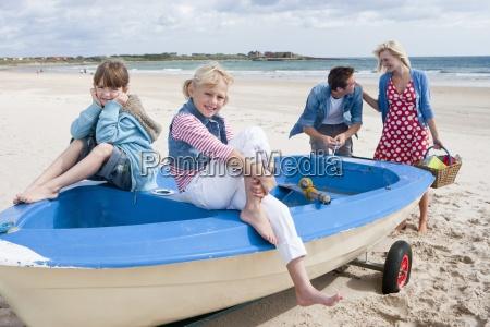 glueckliche familie im boot am strand
