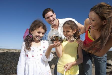 family holding crab on sunny beach