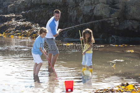 father fishing with daughter and son