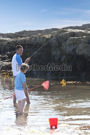 father and son fishing in tide