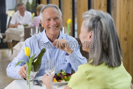 happy man pouring white wine for