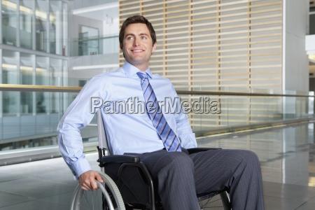 smilende forretningsmand i korestol