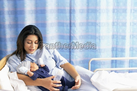 mother holding baby son in hospital