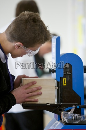 boy with goggles using woodworking machinery