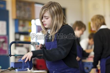 girl using saw in school workshop