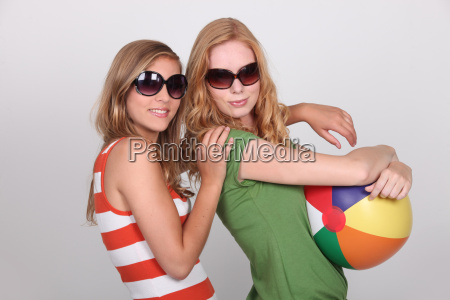 two teenagers wearing sunglasses holding beach