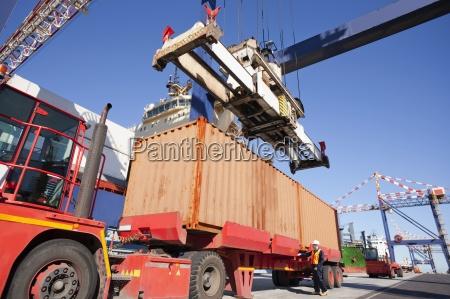 crane unloading cargo container onto lorry