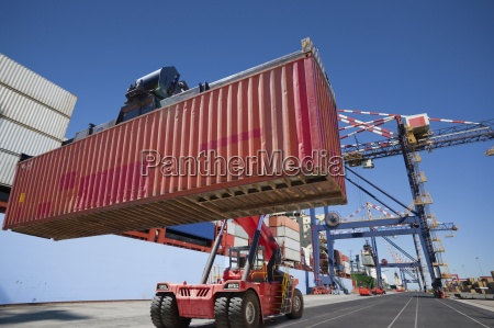 mobile crane moving cargo container at