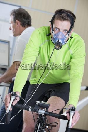 radfahrer mit maske auf heimtrainer in