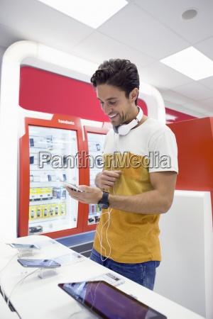 laechelnder mann mit kopfhoerer mit digitalen