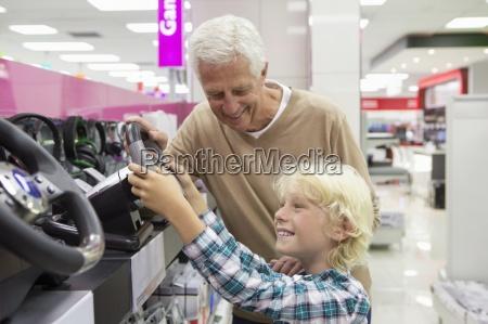 grossvater beobachten enkel mit lenkrad videospiel