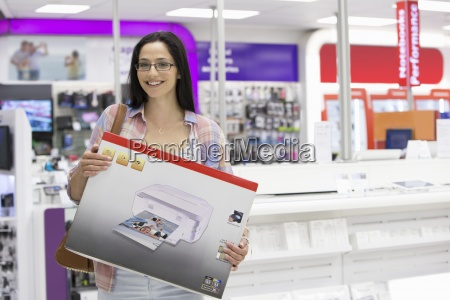 portrait of smiling woman holding printer