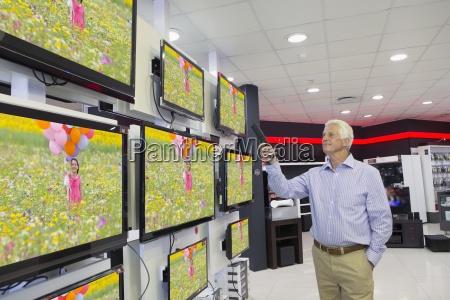 senior man looking at flat screen
