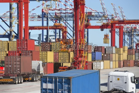 cranes loading cargo containers onto trucks