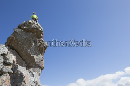 male rock climber on top of