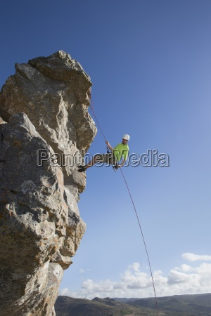 male rock climber abseiling down rock