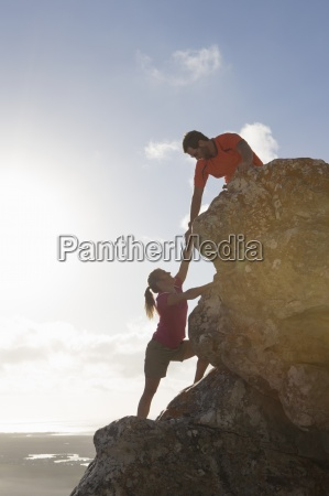 male rock climber helping woman up