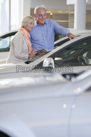 couple with brochure looking at car