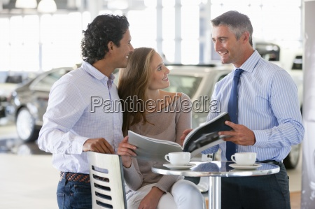 salesman and couple looking at brochure