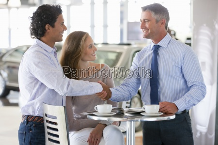 salesman and customer shaking hands at