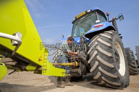 landwirt befestigt landausruestung fuer traktorendarsteller