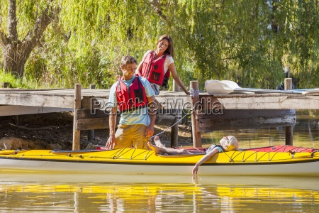 parents in life jackets watching daughter