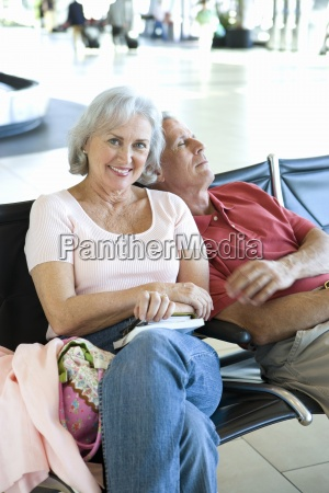 senior couple sitting in airport departure